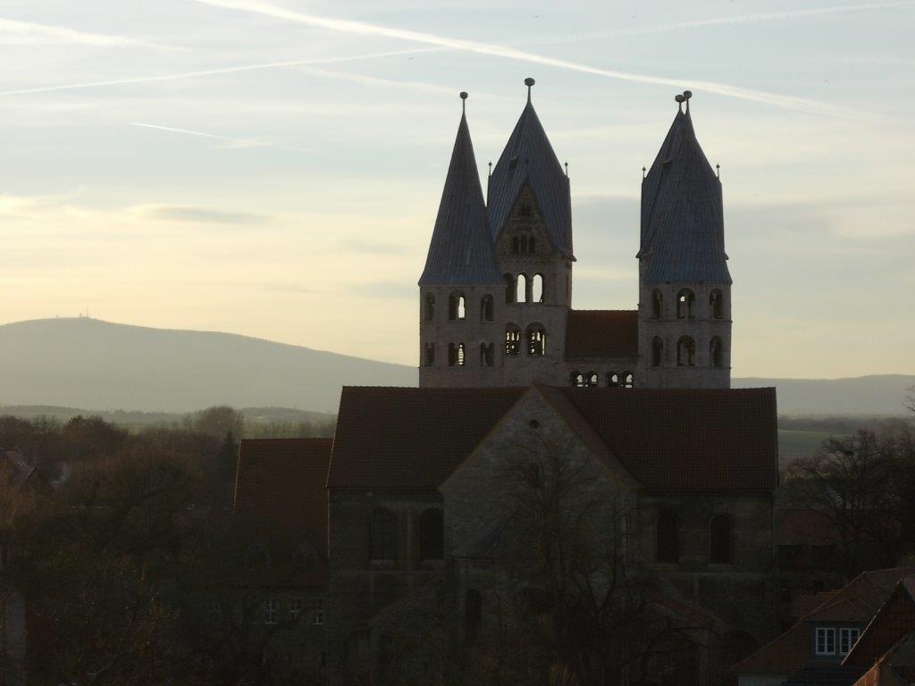 Foto vom Dom zur Liebfrauenkirche in der Abenddämmerung, im Hintergrund der Brocken